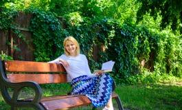 Madame apprécient la poésie dans le jardin Appréciez la rime Coupure blonde de sourire heureuse de prise de femme détendant dans  photographie stock libre de droits