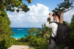 Madame assez jeune avec des jumelles à la côte Photographie stock