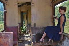 Madame avec le vin rouge à la fenêtre d'un vieux train Photographie stock libre de droits