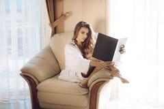 Madame avec le visage occupé dans le peignoir lit le livre près de la fenêtre photographie stock
