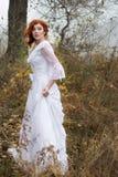 Madame avec les cheveux rouges dans la robe blanche de vintage dans la forêt Image libre de droits