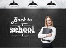 Madame avec un dossier noir pense à la future année universitaire Mots : 'de nouveau à l'école' sont écrits sur le chalkboa noir Photos libres de droits