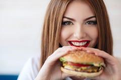 Madame avec un hamburger pour une table dans un café Photographie stock