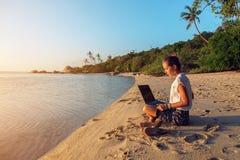 Madame avec un ordinateur portable sur la plage Image stock
