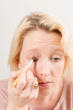 Madame blonde Applying Eyeshadow images libres de droits