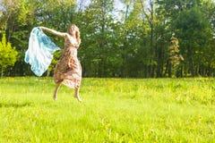 Madame caucasienne heureuse et sautante positive Running en parc d'été avec le foulard de vol images stock