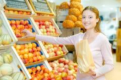 Madame choisissant des nectarines tenant le sac de papier photos stock