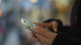 Madame dactylographiant sur le smartphone, se tenant au centre commercial, connexion libre de wifi banque de vidéos
