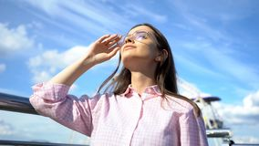 Madame dans des lunettes de soleil recherchant au ciel bleu, appréciant la nature et la liberté, jeunesse images libres de droits