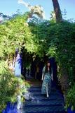 Madame dans des promenades bleues et jaunes de robe en bas des étapes de jardin photos libres de droits