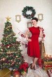 Madame dans la robe rouge parmi la décoration de Noël Photographie stock
