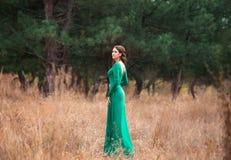 Madame dans les dres verts luxuriants d'un luxe Photographie stock libre de droits