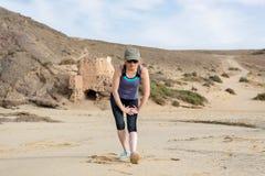 Madame dans les vêtements de sport étirant la jambe pour l'échauffement de forme physique photos libres de droits