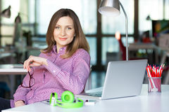 Madame de sourire d'affaires dans les vêtements décontractés se reposant au Tableau de bureau Photos stock