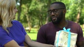 Madame donnant le cadeau de Noël à l'ami d'afro-américain tout en se reposant en parc banque de vidéos