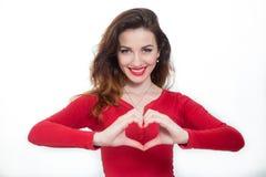 Madame en rouge embrassant et montrant la forme de coeur photos libres de droits