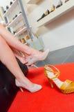 Madame essayant sur des chaussures de paires dans la boutique Photo stock
