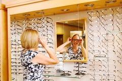 Madame essayant sur des verres Photos libres de droits