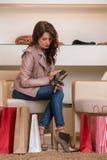 Madame essayant sur plusieurs paires de nouvelles chaussures dans le magasin images stock