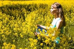 Madame est engagée dans la méditation en parc de ville parmi les fleurs jaunes Belle femme faisant la méditation de yoga en parc Photographie stock libre de droits