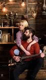 Madame et l'homme avec la barbe sur les visages rêveurs étreint et joue la guitare Concept romantique de soirée Les couples dans  Photo stock
