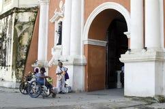 Madame, homme aveugle près de mendiant handicapé dans le fauteuil roulant au portail de porte de yard d'église photos libres de droits