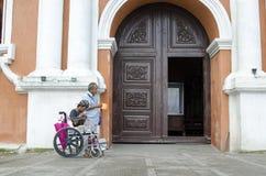 Madame, homme aveugle près de mendiant handicapé dans le fauteuil roulant au portail de porte de yard d'église photo libre de droits
