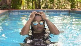 Madame indienne luxueuse Swimming dans la piscine portant Sunglass des vacances de week-end images stock
