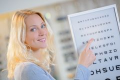 Madame indiquant le diagramme du ` s d'opticien photographie stock