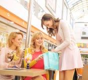 Madame montrant à ses amies quelques achats Photographie stock libre de droits