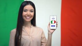 Madame montrant le téléphone portable avec pour apprendre l'appli italien, drapeau sur le fond, éducation banque de vidéos