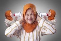 Madame musulmane asiatique Close Her Ears a distrait par voix intérieure image stock