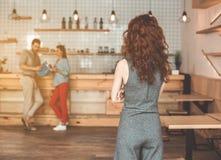 Madame observant son homme flirter avec la fille dans le cafétéria Image stock