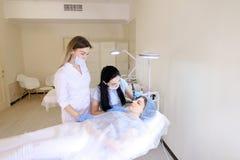 Madame obtenant la constante professionnelle composent par le cosmetologist et l'infirmière Image stock