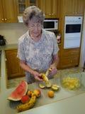Madame pluse âgé Preparing Fruit Salad. Images libres de droits