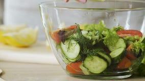 Madame préparant la salade fraîche avec l'huile et le stirring d'olive il dans la cuvette, consommation saine clips vidéos