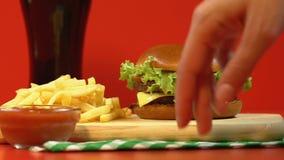 Madame prenant l'hamburger du prêt-à-manger combiné, pommes frites avec de la sauce du plat en bois clips vidéos