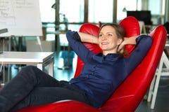 Madame réussie de sourire d'affaires dans la chaise rouge de bureau de relaxation Images libres de droits