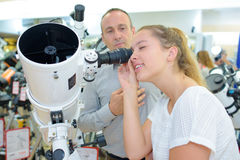 Madame regardant dans le télescope puissant de lentille photographie stock