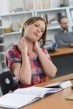 Madame reposée au bureau avec le cou raide photographie stock libre de droits