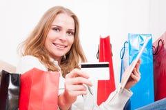 Madame s'étendant sur le divan tenant le comprimé montrant la carte de crédit Photos stock