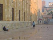 Madame s'asseyant dans la ruelle touchant la mosquée d'Al-Hussein Image stock