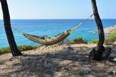 Madame s'asseyant dans un hamac attaché à deux arbres sur une roche près d'une mer bleue un jour ensoleillé avec les cieux bleus Photos libres de droits
