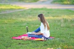 Madame s'asseyant en parc et parlant sur Skype par l'intermédiaire d'un ordinateur portable avec des écouteurs Photo stock
