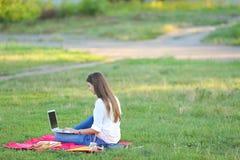 Madame s'asseyant en parc et parlant sur Skype par l'intermédiaire d'un ordinateur portable avec des écouteurs Image stock