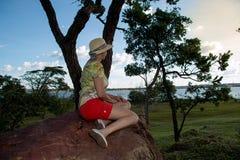 Madame Sitting sur une grande roche observant le coucher du soleil Image libre de droits