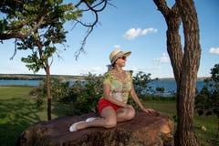 Madame Sitting sur une grande roche observant le coucher du soleil Photo stock