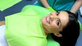 Madame souriant à la caméra après opération réussie d'art dentaire, soin professionnel photographie stock libre de droits