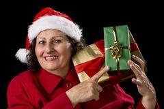 Madame supérieure avec Santa Cap Points aux cadeaux enveloppés Photographie stock libre de droits