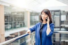 Madame supérieure enthousiaste Talking d'affaires au téléphone Image stock
